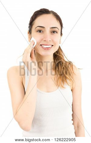 Attractive cauasian woman cleaning her make up with cotton ball. Isolated on white background.