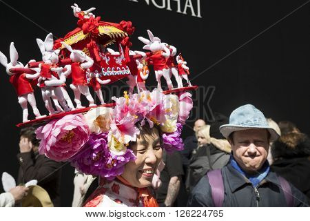 NEW YORK - MAR 27 2016: A woman wearing an Easter bonnet made of toy rabbits carrying a Chinese jiao on 5th Ave Easter Sunday for the traditional Easter Bonnet Parade in Manhattan on March 27, 2016.