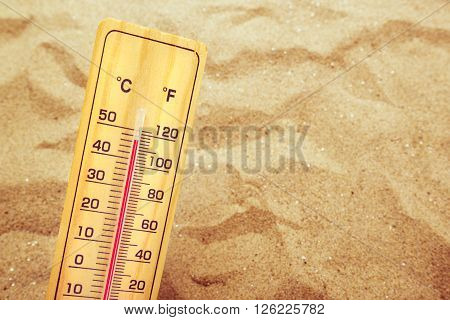 Extremely high temperatures thermometer with celsius and farenheit scale on warm desert sand.