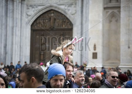 NEW YORK - MAR 27 2016: A young girl wearing Easter Bunny ears sits on a mans shoulders above the crowd on 5th Ave Easter Sunday at the traditional Easter Bonnet Parade in Manhattan on March 27, 2016.