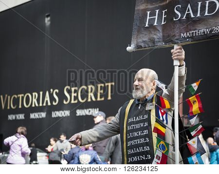 NEW YORK - MAR 27 2016: A man holding a religious sign stands on 5th Avenue in front of Victorias Secret on Easter Sunday during the traditional Easter Bonnet Parade in Manhattan on March 27, 2016.