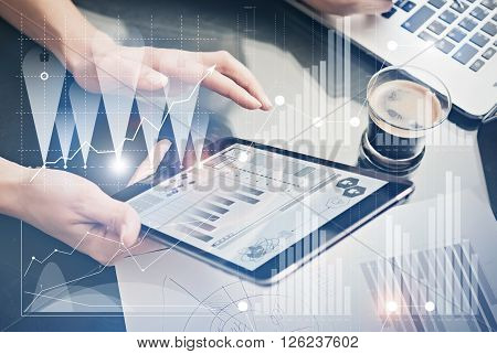 Photo female hands holding modern tablet.Account managers working new private banking project office.Using electronic devices. Graphics icons, worldwide stock exchanges interface on screen.