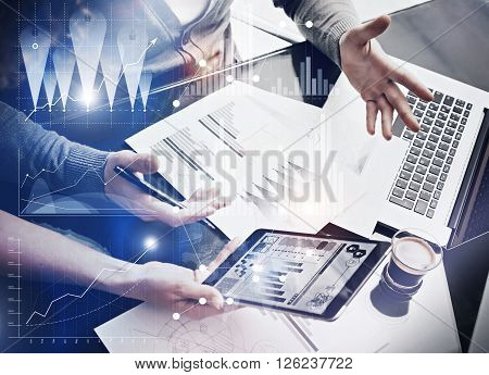 Photo business team brainstorming.Finance department managers working new global project in office.Using electronic devices.Graphics icons, worldwide stock exchanges interface on the screen.