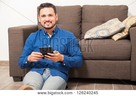 Happy Hispanic Man Using An E-reader At Home