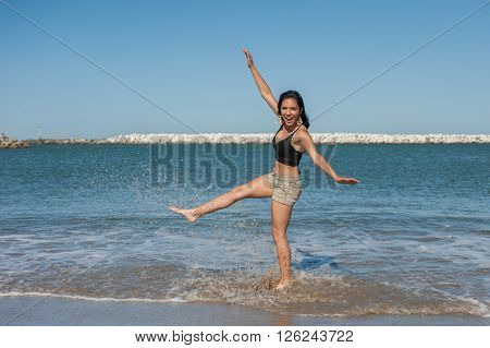 Young and energetic Latina beauty kicking ocean water.