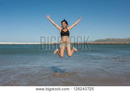 Young and energetic Latina beauty jumping over ocean water.