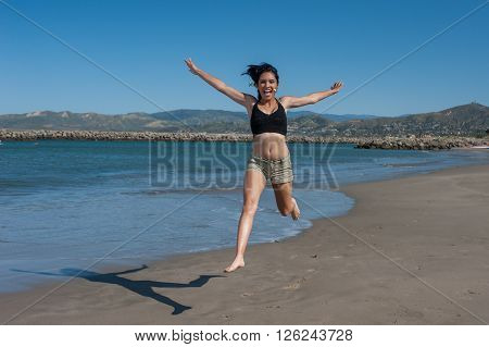 Young and energetic Latina beauty leaping across ocean shoreline. ** Note: Soft Focus at 100%, best at smaller sizes