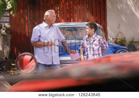 Family and Generation gap. Old grandpa spending time with his grandson. The senior man talks vintage car with the boy and lean against the hood of an automobile from the 60s