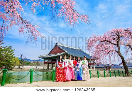 SEOUL SOUTH KOREA - APRIL 6: Gyeongbokgung Palace with cherry blossom in spring and tourists with Hanbok dress on April 6 2016 in Seoul South Korea.