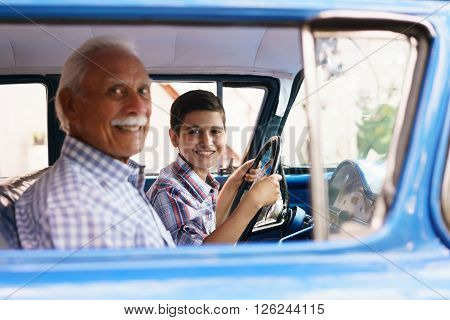 Family and Generation gap. Old grandpa spending time with his grandson. He teaches him to drive. The boy holds the volante of a vintage car from the 60s. They both smile happy looking at camera.