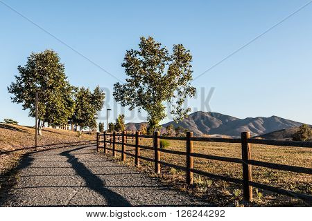 Pathway with trees and mountain range in distance at Mountain Hawk Park in Chula Vista, California.