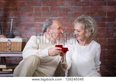 Mature couple drinking wine together at home