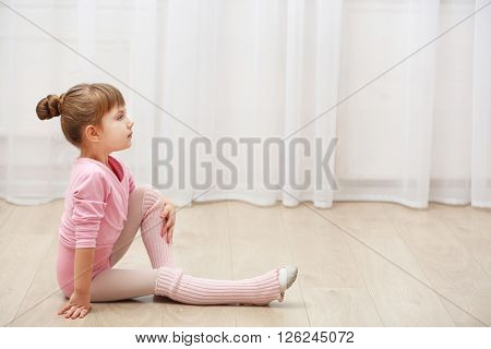 Little cute girl in pink leotard sitting on floor at dance studio