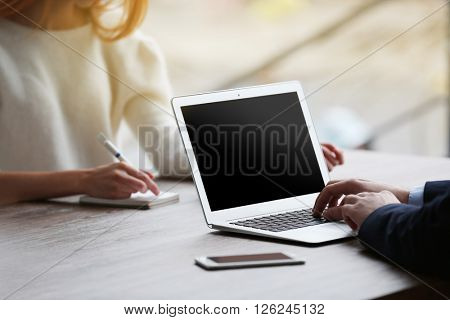 Businessman using laptop and young woman taking notes
