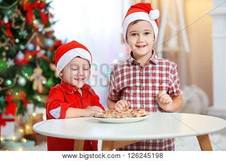 Two cute small brothers eating cookies on Christmas decoration background