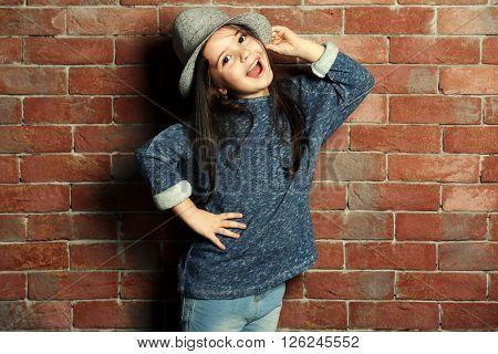 Portrait of little fashion kid girl on bricks wall background