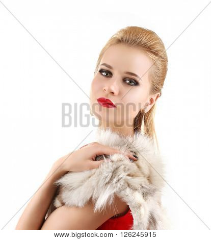 Young beautiful blonde girl wearing perfect makeup and red dress posing in a fur over white studio background