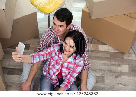 Young couple taking picture on the floor of their new house. Close up.