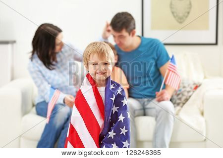 Parents and their son wrapped in a USA flag