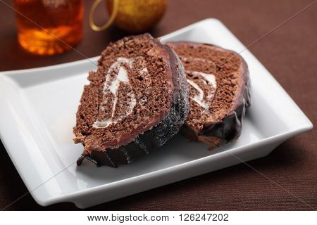 Slices of Yule log cake topped with chocolate on a Christmas table