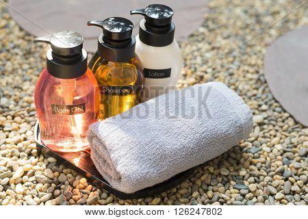 Bathroom amenity set on pebbles floor, bath gel, shampoo and conditioner