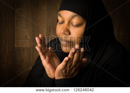 African muslim woman weiring a black veil in prayer