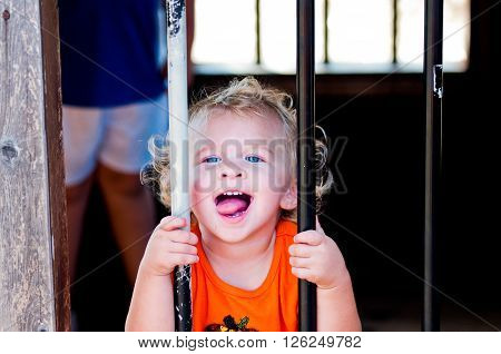 Close up of curly blonde haired toddler girl behind bars at a pumpkin festival.