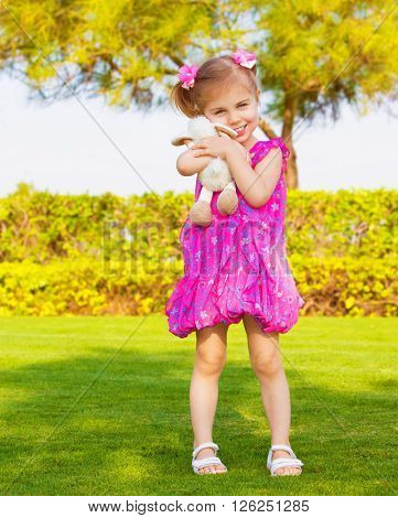 Photo of cute little girl holding in hands soft toy, sweet baby playing outdoors, adorable small female having fun on backyard in spring, pretty kid wearing pink dress, happy childhood concept