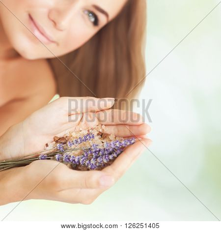 Woman at beauty salon, beautiful female at spa holds lavender flower and bath salt, aromatherapy herbal anti-stress treatment for health of mind and soul, body skin face and hair care, selective focus