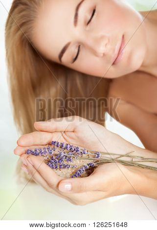Woman with closed eyes at spa salon, holding lavender and sea salt, enjoying aromatherapy herbal anti-stress treatment for health of mind and soul, body skin face and hair care, selective focus
