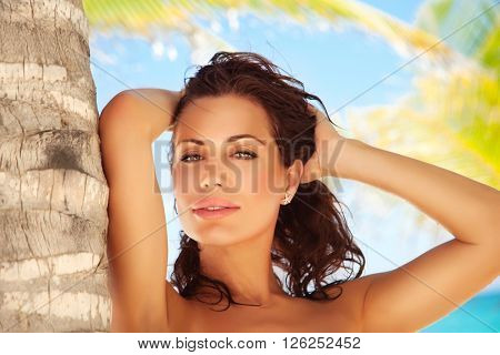 Portrait of a beautiful gorgeous female standing on the beach near palm tree, woman enjoying sunny days on tropical resort, happy summer holidays on Caribbean islands