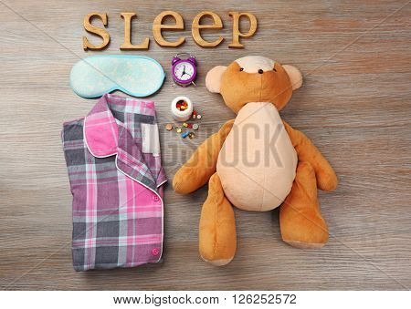 Word Dream with toy, pajamas and mask on a wooden background