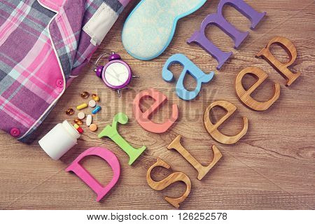 Words Sleep and Dream with pajamas on a wooden background