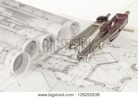 rolls of architecture blueprints, house plans &  compasses