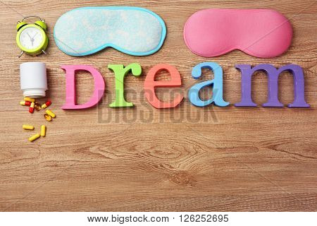 Word Dream with pills and sleeping masks on a wooden background