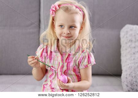 Little girl painting Easter egg indoors
