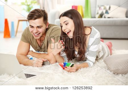 Young couple doing online shopping with laptop and credit card lying on fur carpet indoors