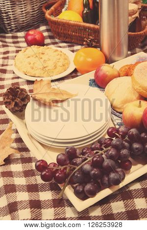 Composition of plates, fresh fruits and baking on checkered tablecloth