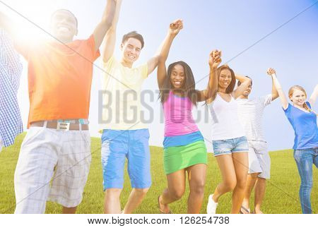 Multi-Ethnic Teenagers Outdoors Holding Hands Celebrating Concept