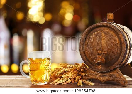 Mug and barrel of cold fresh beer on table, on dark pub background