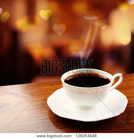 Cup of coffee on table on blured cafe background