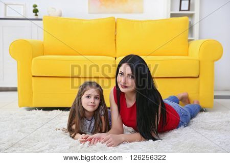 Mother and daughter lying on the carpet beside yellow sofa.
