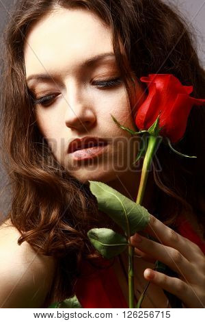 Studio portrait of sensual beautiful woman with rose