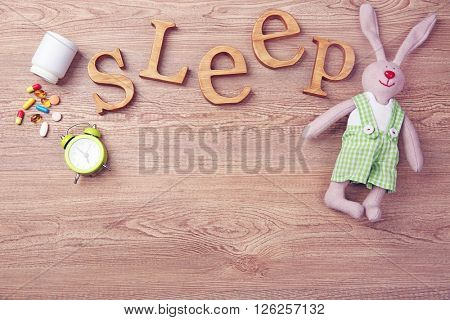 Word Sleep with pills and little toy  on a wooden background