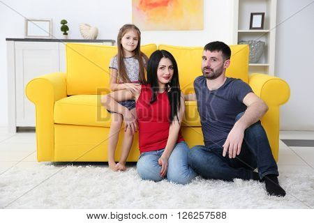 Parents and their daughter sitting on the floor beside yellow sofa.