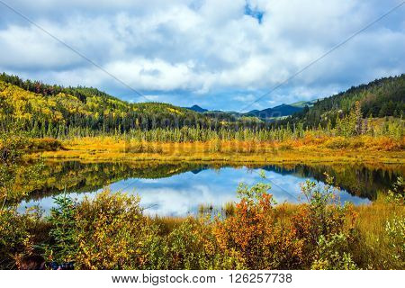 Charming Patricia Lake amongst the evergreen forests and distant mountains. Warm autumn in the Rocky Mountains of Canada