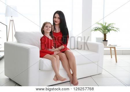 Mother and daughter sitting on the white sofa.