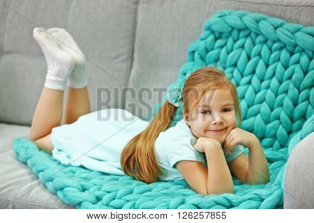 Happy small girl lying on couch