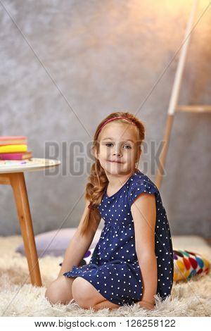 Beautiful small girl sitting on carpet in light room