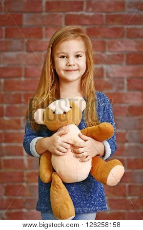 Beautiful small girl with teddy bear against brick wall background